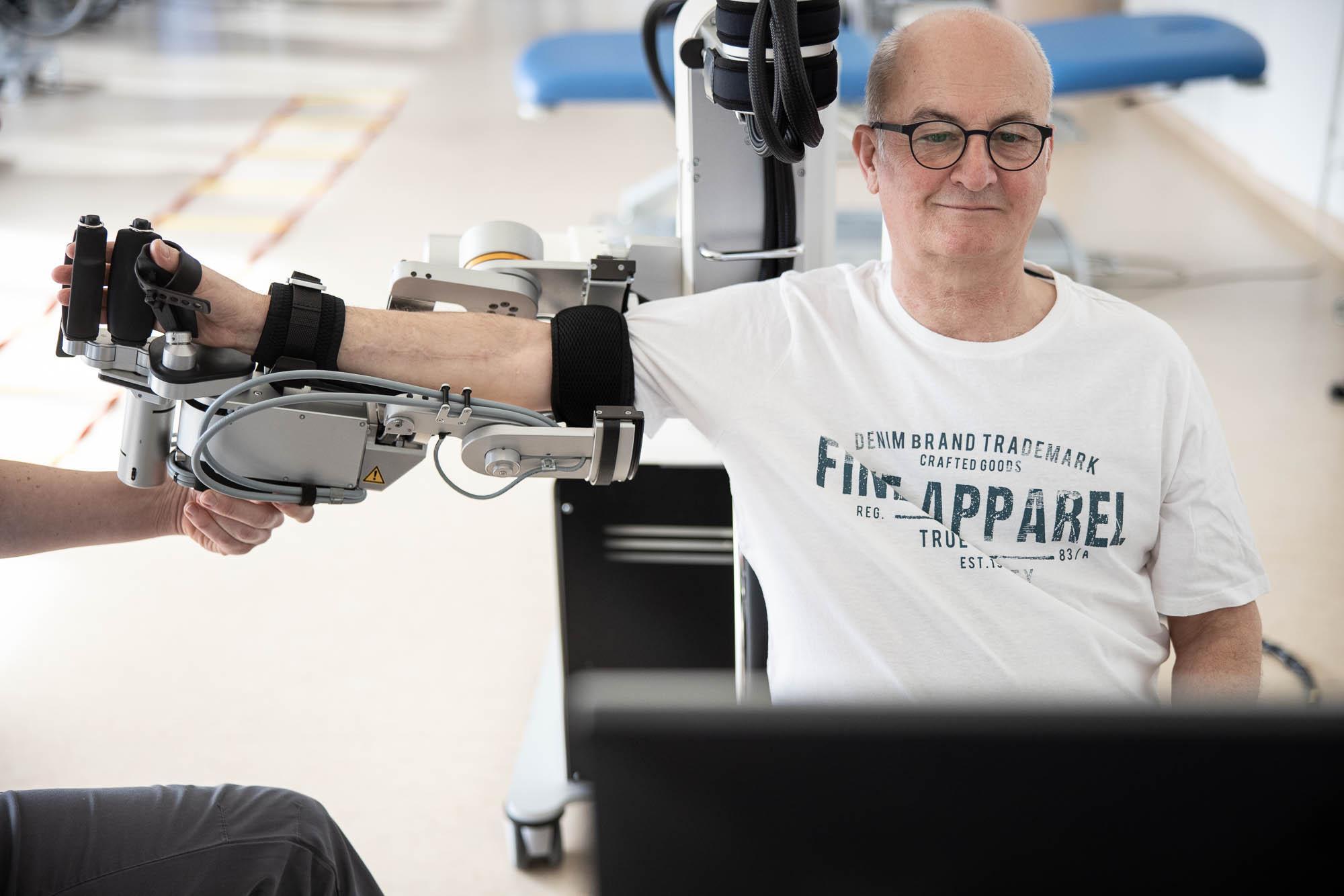 Patient beim Training mit dem Armroboter